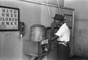 A Black man stands in front of a water-drinking station in segregation-era America.
