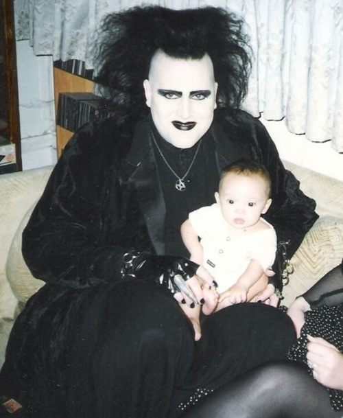 Goth father with white made up face, black eyeshadow and lipstick, wild black hair, and all black attire. He is holding his infant son on his knee.